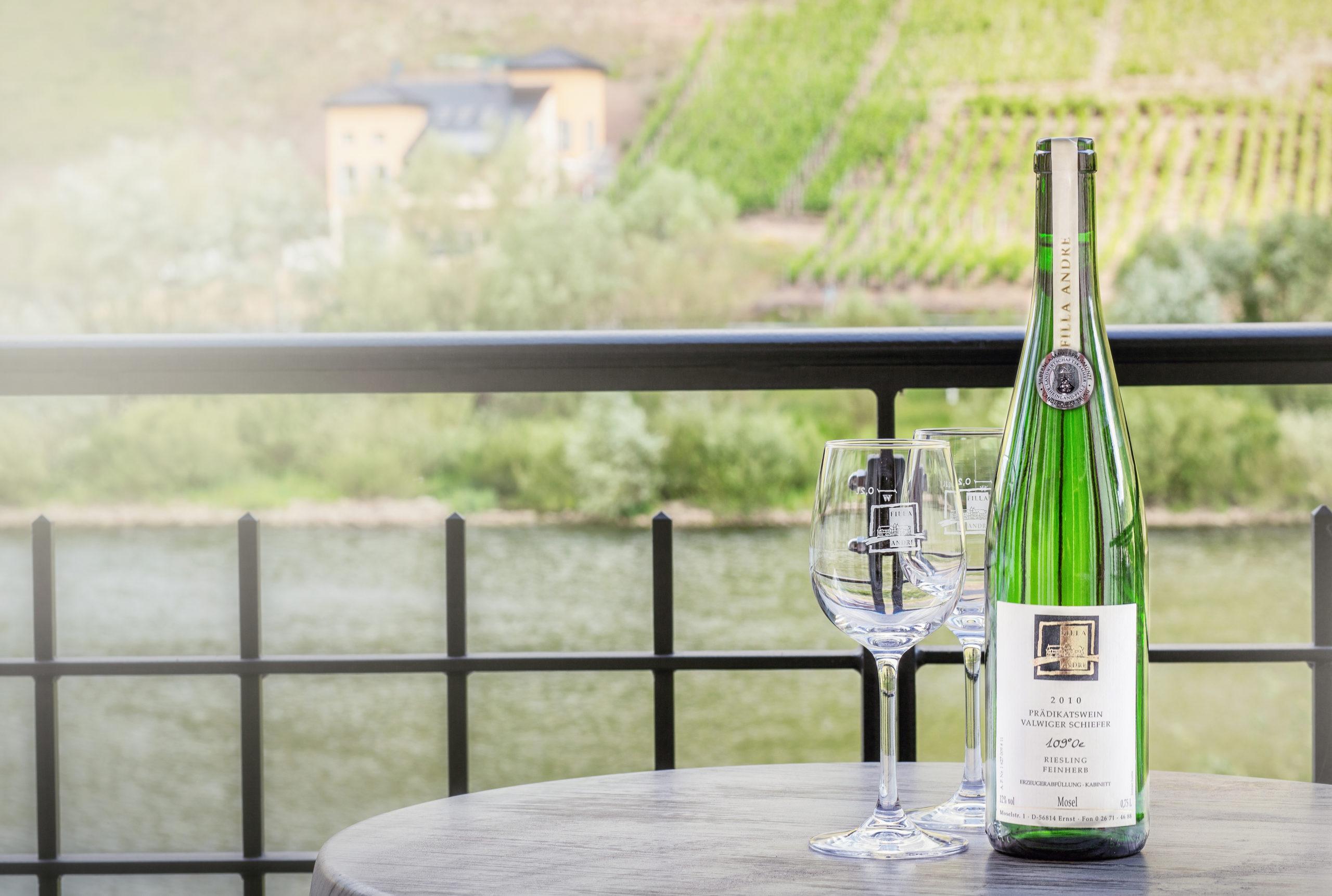 Weinflasche mit Glas auf kleinem Tisch Mosel und Weinberge im Hintergrund