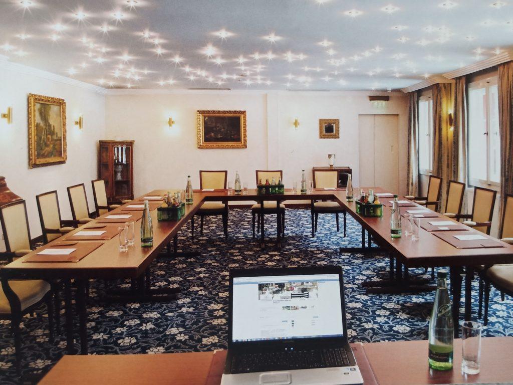 Tagungsraum mit Tischen und Stühlen, an der Decke Strahler