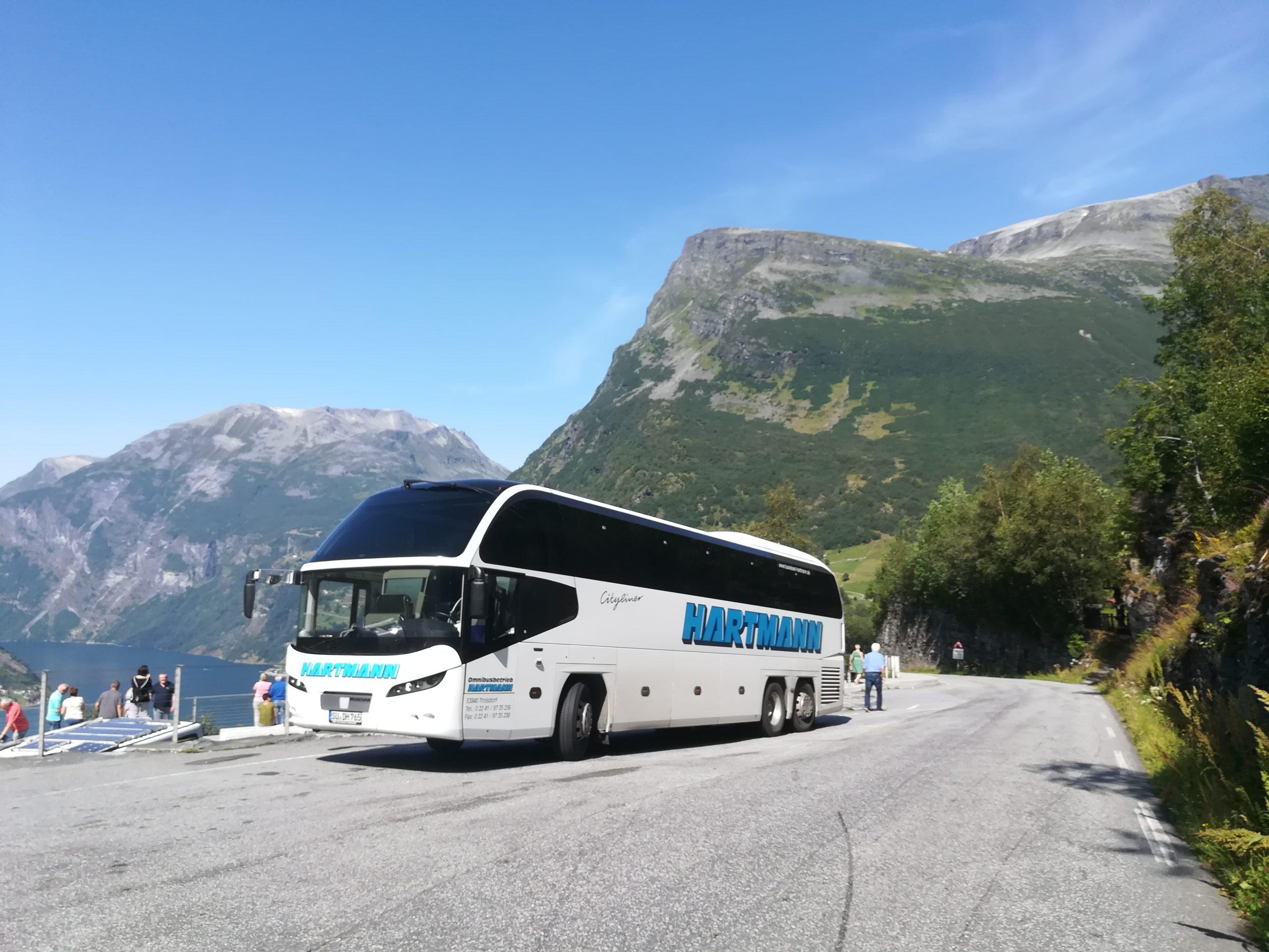 Firmenreisen Skandinavien Nordeuropa Norwegen weißer Bus mit getönten Scheiben kurz vor dem Geiranger im Hintergrund Berge