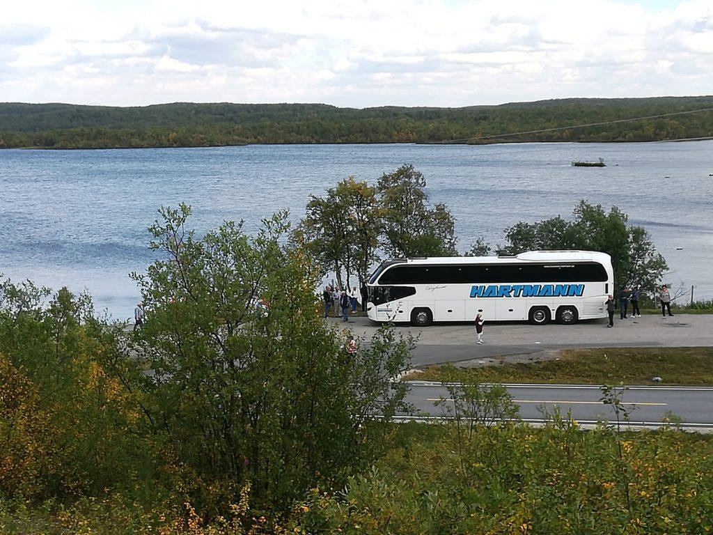Busreise Gruppenreise weißer Reisebus mit getönten Scheiben im Hintergrund ein See Norwegen