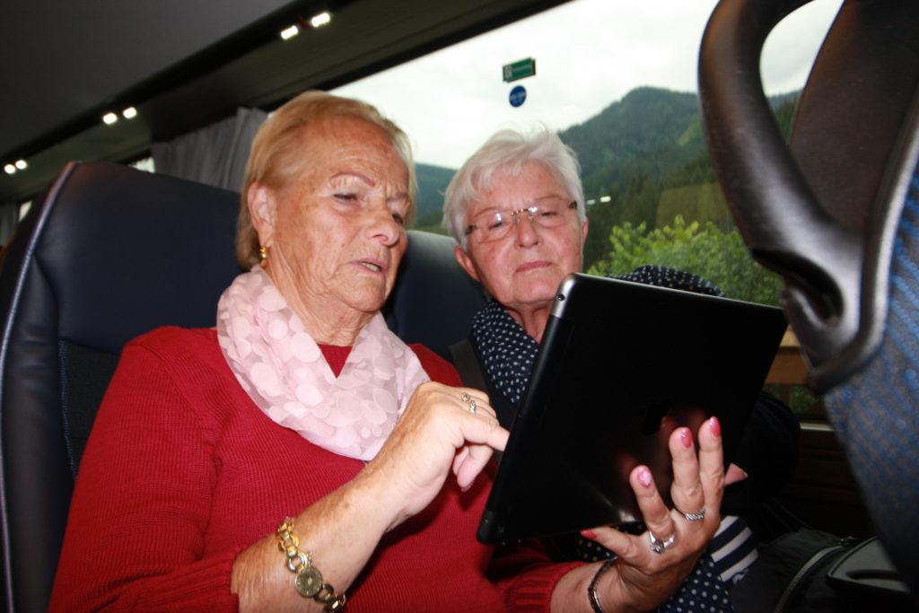 Reisende die sich mit dem Tablet im Bus beschäftigen
