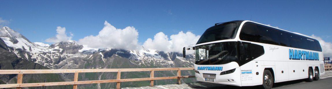 weißer Reisebus Busstopp Österreich Berge im Hintergrund