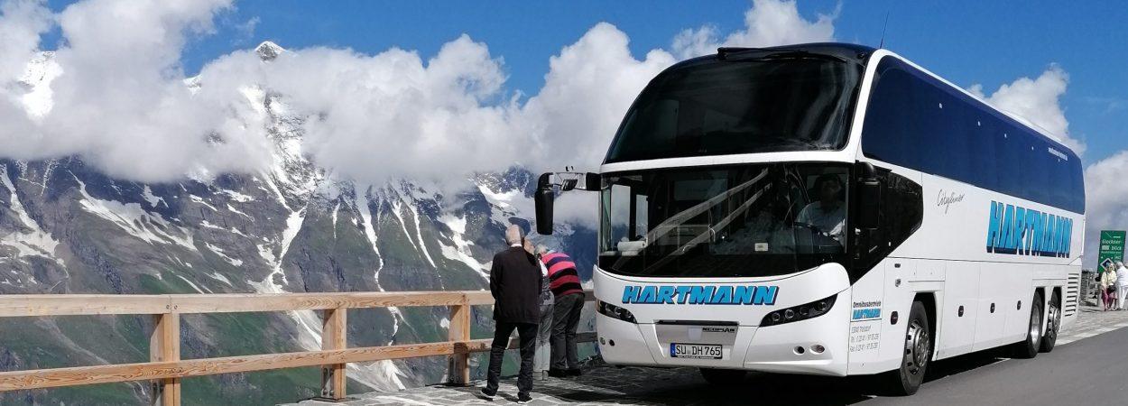 Busvermietung weißer Reisebus mit getönten Scheiben vor dem Großglockner Berge im Hintergrund