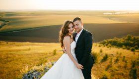 Hochzeitspaar im Sonnenlicht vor einem Feld