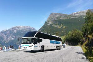 weißer Bus mit getönten Scheiben kurz vor dem Geiranger im Hintergrund Berge