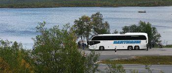 Busreise Gruppenreise weißer Reisebus mit getönten Scheiben im Hintergrund ein See