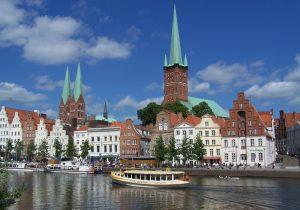 Busreise Blick auf Lübecker Kirchen und landestypischen Häuserzug von der Trave aus gesehen