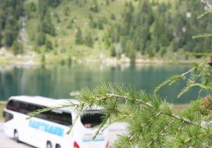 Busreise weißer Reisebus mit getönten Scheiben am See