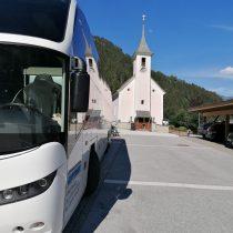 weißer Reisebus kleine Kapelle im Hintergrund