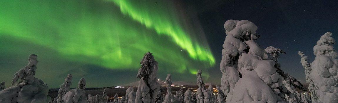Verschneites Finnland im Dunklen, grüne Polarlichter in Hintergrund