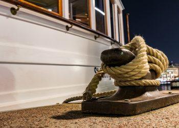 weißes Boot was mit einem Schiffstau am Anlieger fest ist