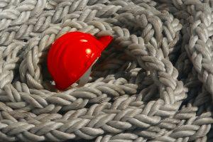 Roter Arbeitshelm im Schiffstau