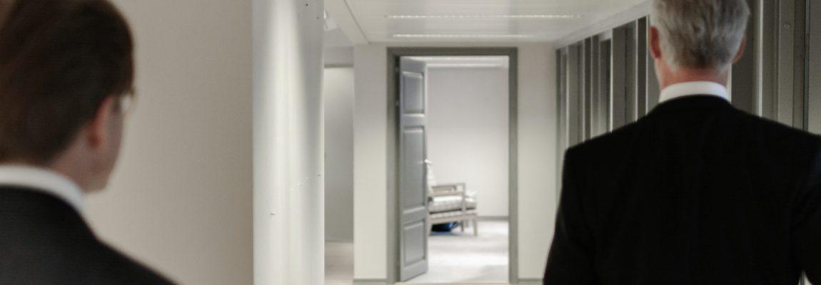 2 Geschäftsleute in dunklem Anzug auf dem Weg in einen Seminarraum