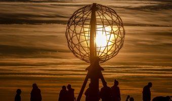Skandinavien Nordeuropa Busreise Norwegen Menschen an der Nordkapkugel die Mitternachssonne im Hintergrund