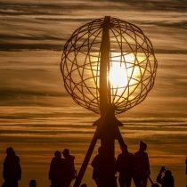 Menschen an der Norkapkugel die Mitternachtssonne im Hintergrund
