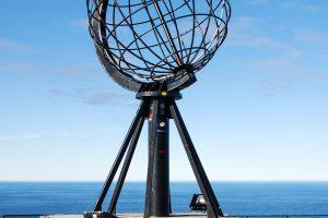 Nordkapkugel, dahinter das Europäische Nordmeer und blauer Himmel